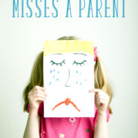 A girl holding up a picture of a sad face over her own face: What to do when your child misses a parent