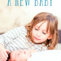 Help your baby adjust to a new baby: Little girl caressing her new baby sibling's head