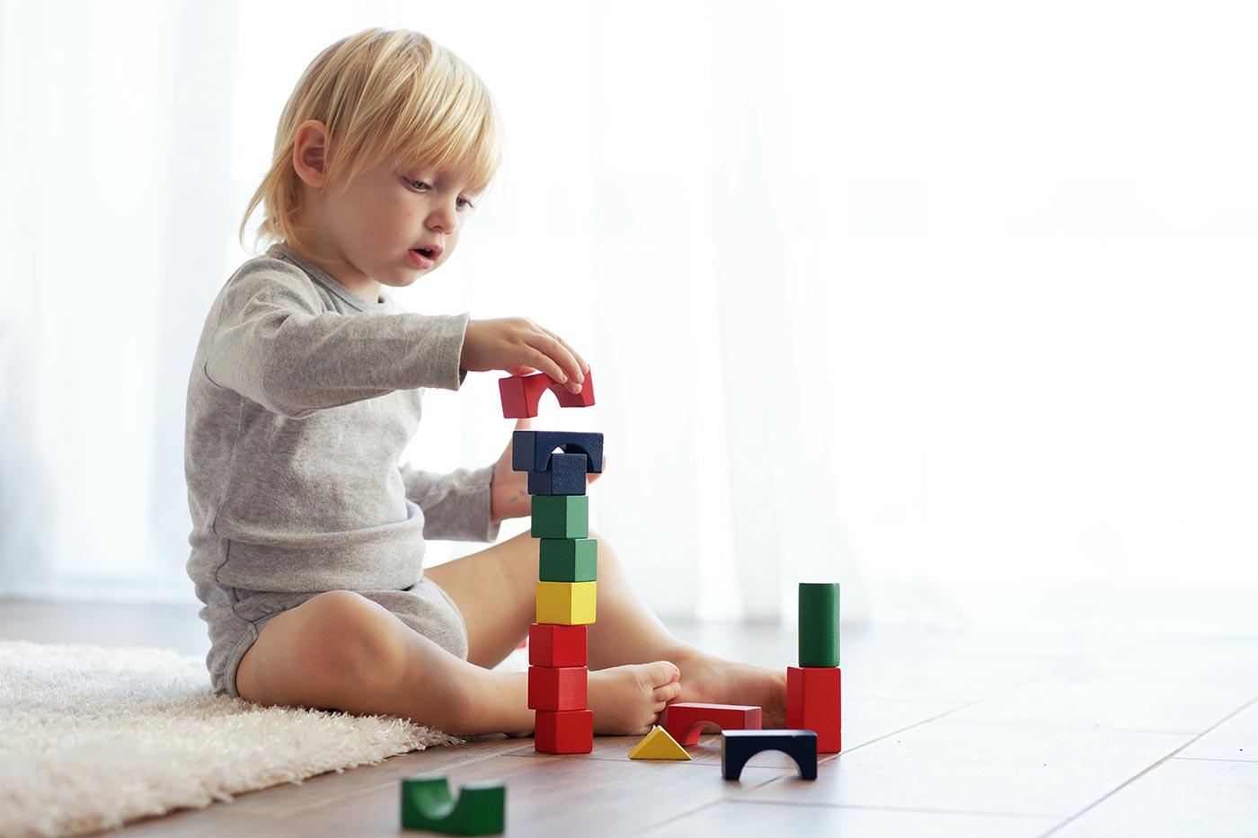 Child stacking wooden blocks