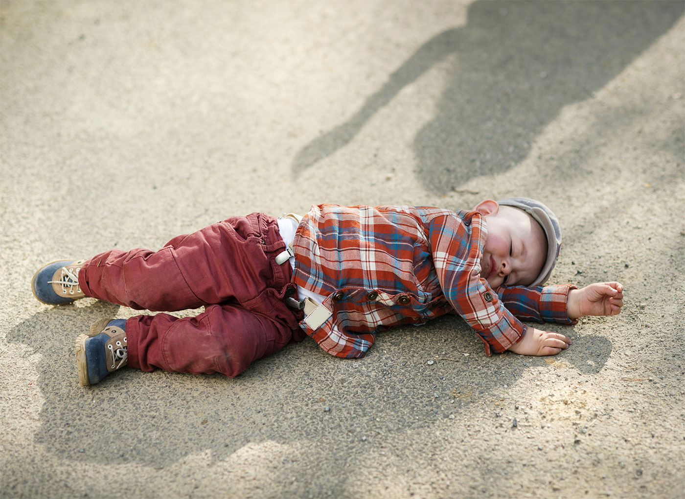 Little boy lying on the ground, throwing a tantrum in public outdoors