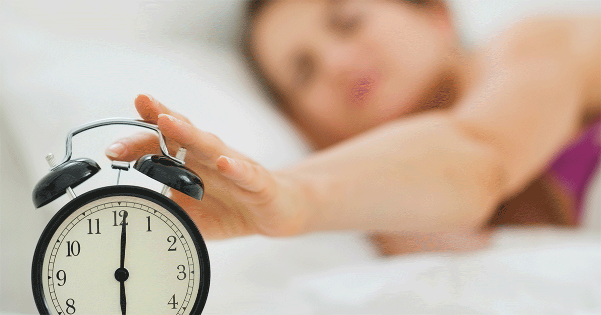 Woman in bed reaching over to turn off her alarm clock