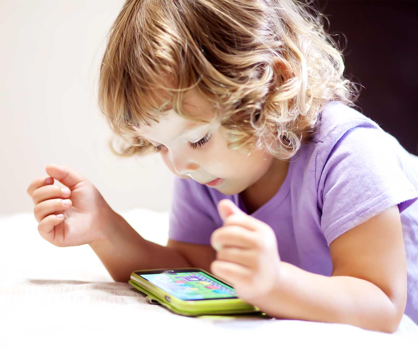 A little girl with a smart phone, redirecting toddler behavior