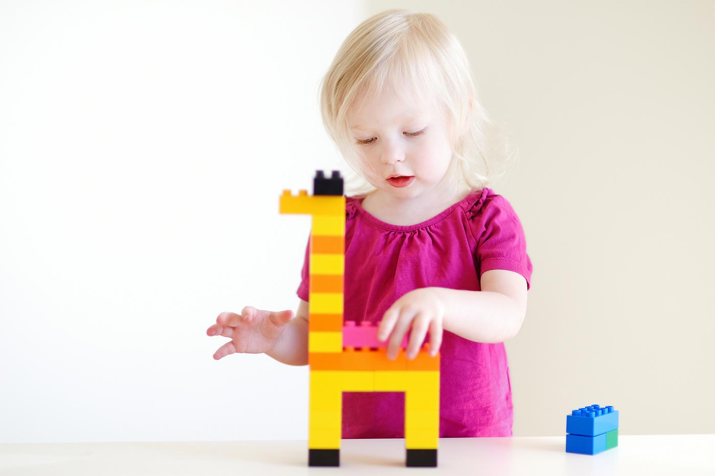 Girl using Lego blocks for independent play
