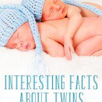 Newborn twin babies, asleep together wearing blue hats