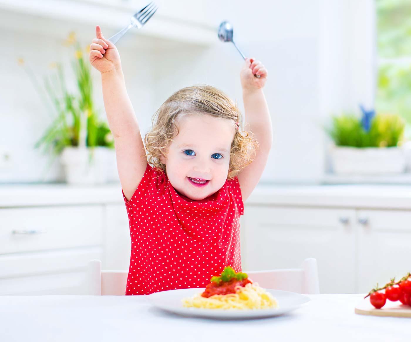 Toddler girl happy to eat spaghetti