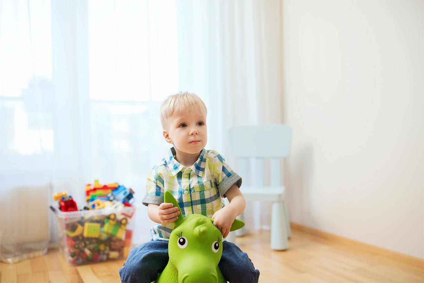 Boy sitting on an inflatable green toy, holding onto the toy's ears, in a play room