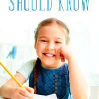 Smiling little girl writing: What every kindergartener should know