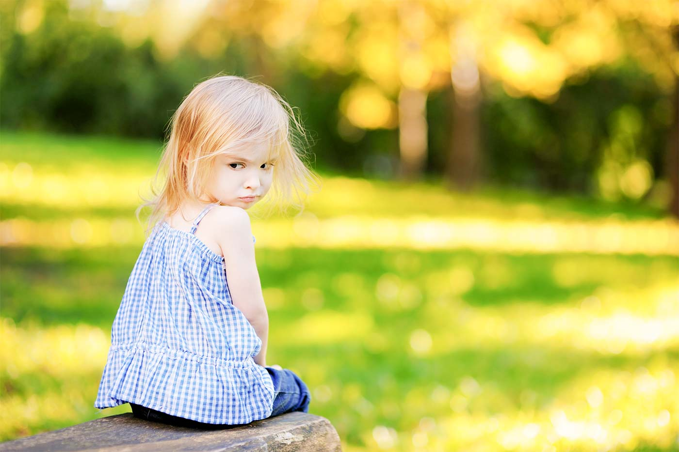 Mad little girl sitting outside with her back turned