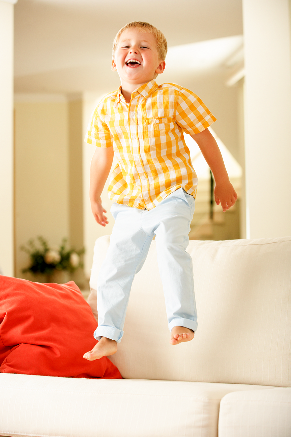 Little boy in a yellow shirt jumping on the couch