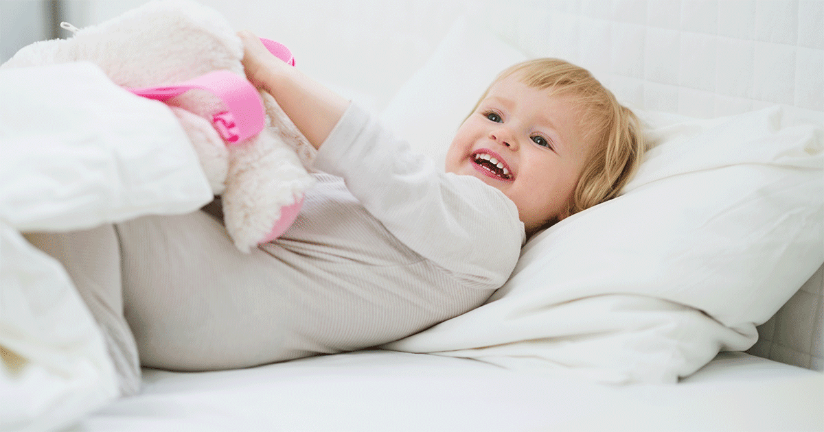 Little girl playing in bed, holding a stuffed animal
