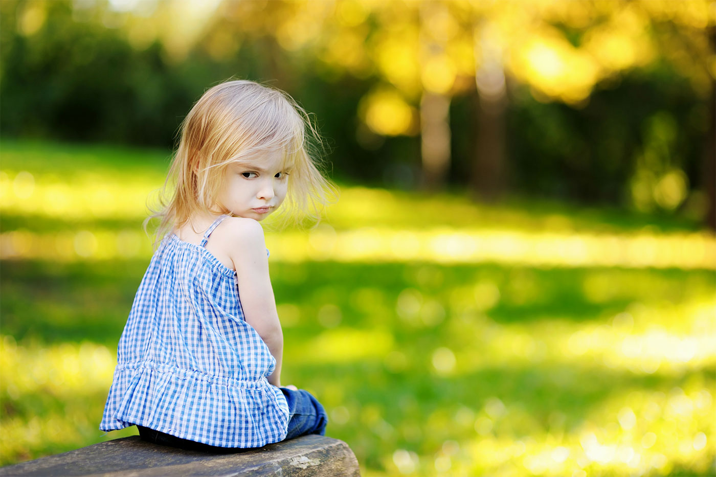 Mad little girl sitting on a rock outdoors, facing backward