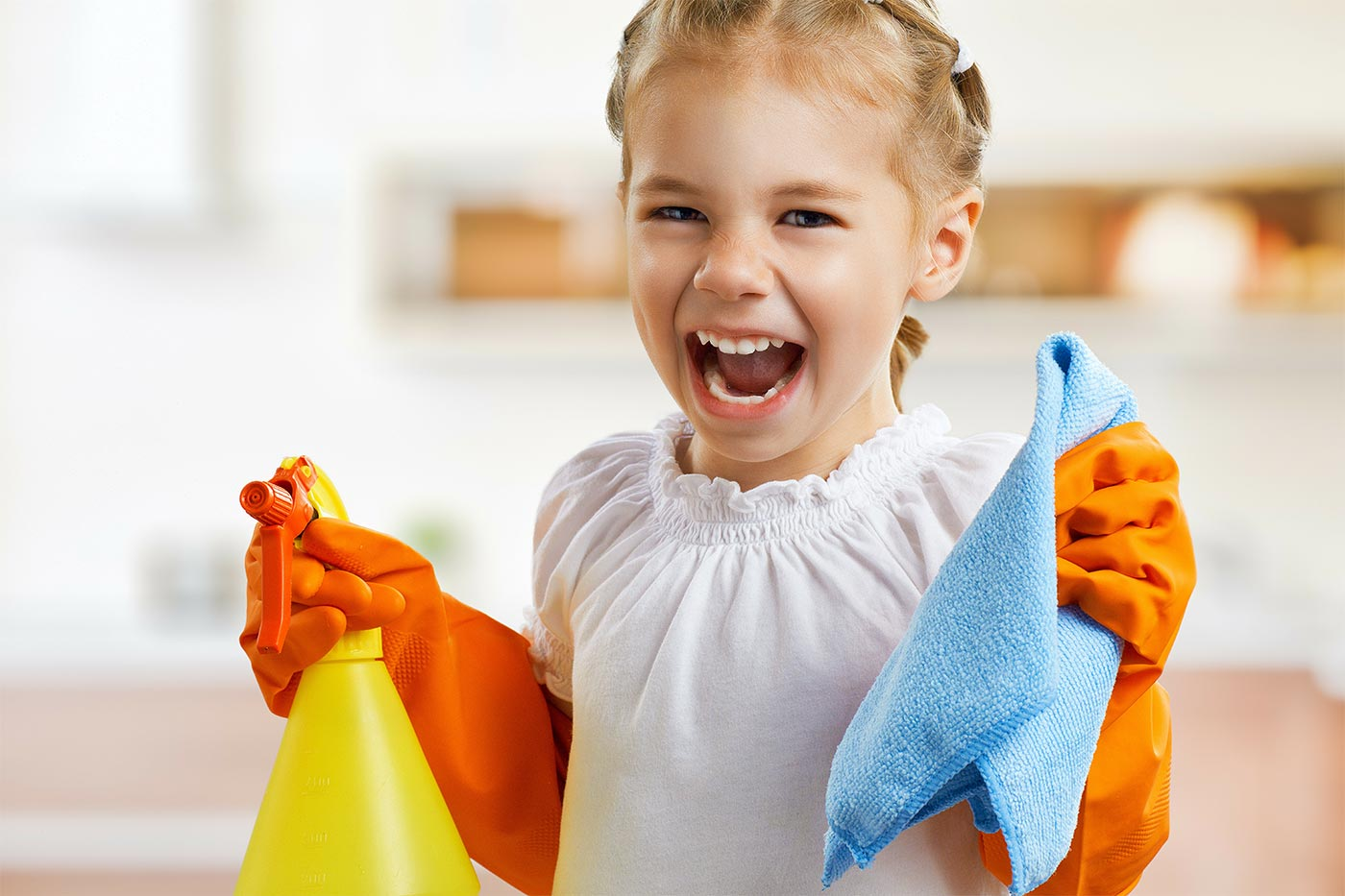 Girl holding a spray bottle and rag, wearing cleaning gloves doing chores