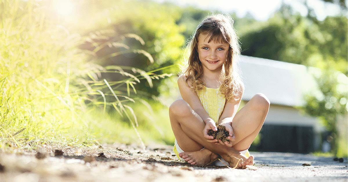 Little girl playing outside and holding dirt