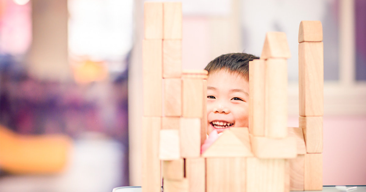 Little boy proud of himself for building a tower of wooden blocks