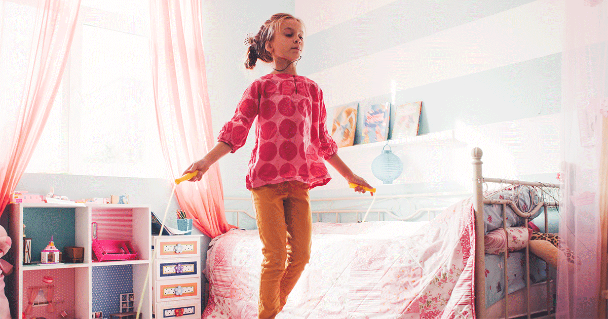 A girl jumping rope in her room