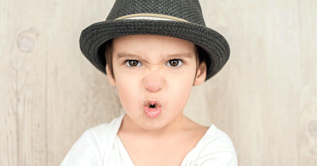 Scowling boy wearing a white shirt and black hat