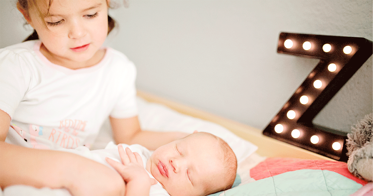 A little girl with her new baby sibling: How to help your child handle a baby crying