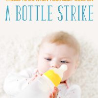 Baby holding an empty milk bottle above him: 9 things to do if your baby goes on a bottle strike