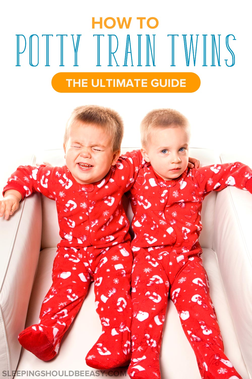 Twin boys in matching red pajamas, sitting on a white chair
