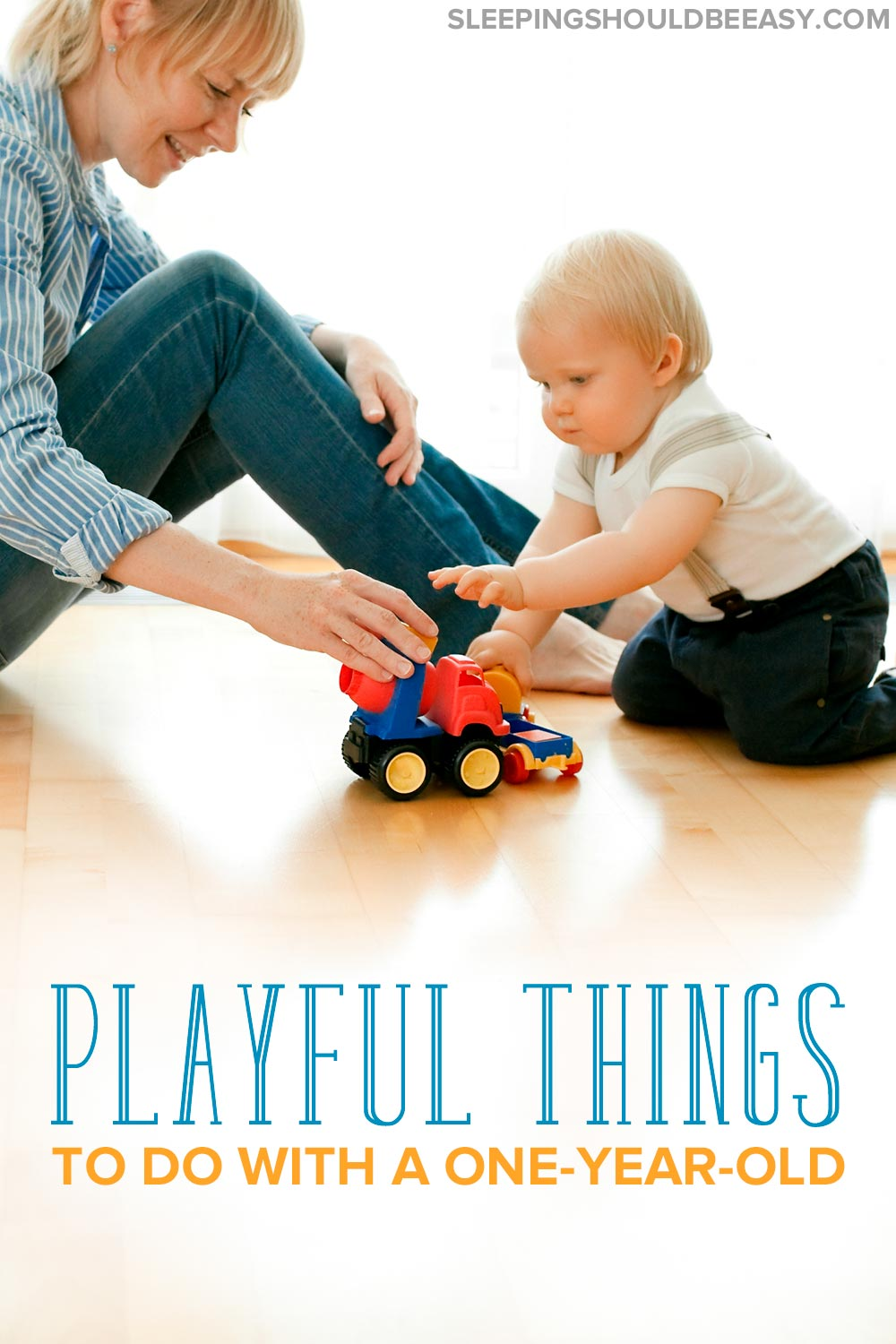 Mom and a 1 year old playing with a toy truck on the floor