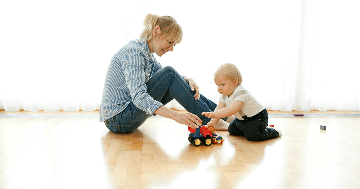 Mom and toddler playing with a toy truck