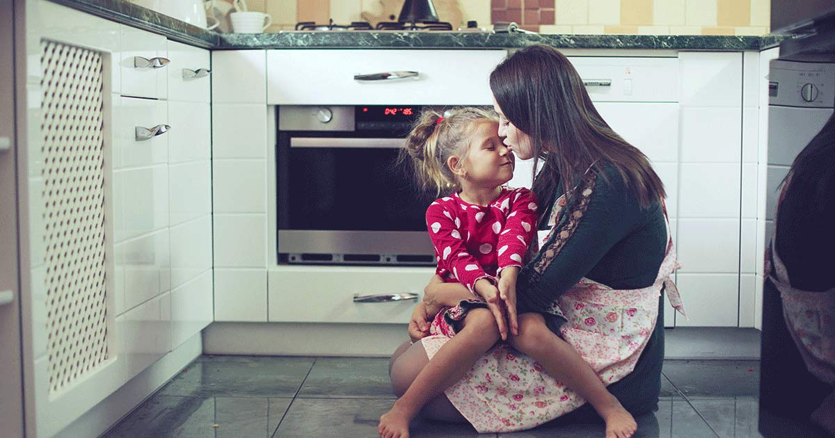 Mom and daughter hugging in the kitchen