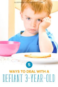 A defiant 3 year old boy at a dinner table, head on his hand, refusing to eat