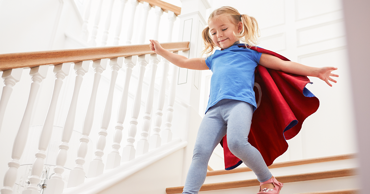 Little girl wearing a cape running down the stairs