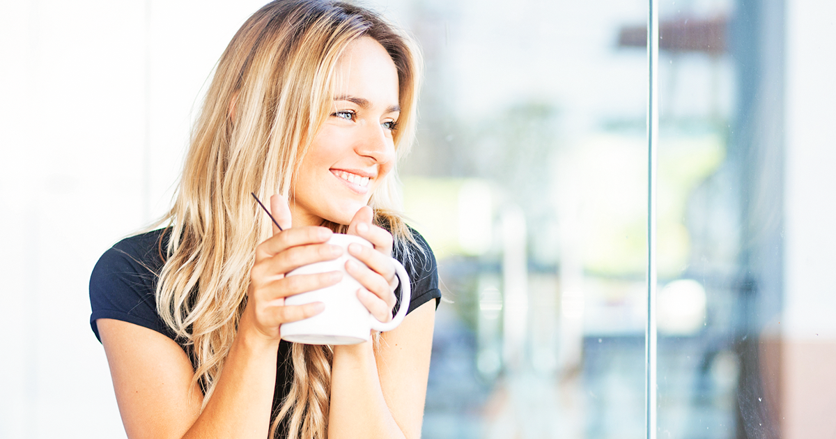 A happy mom holding a cup of coffee