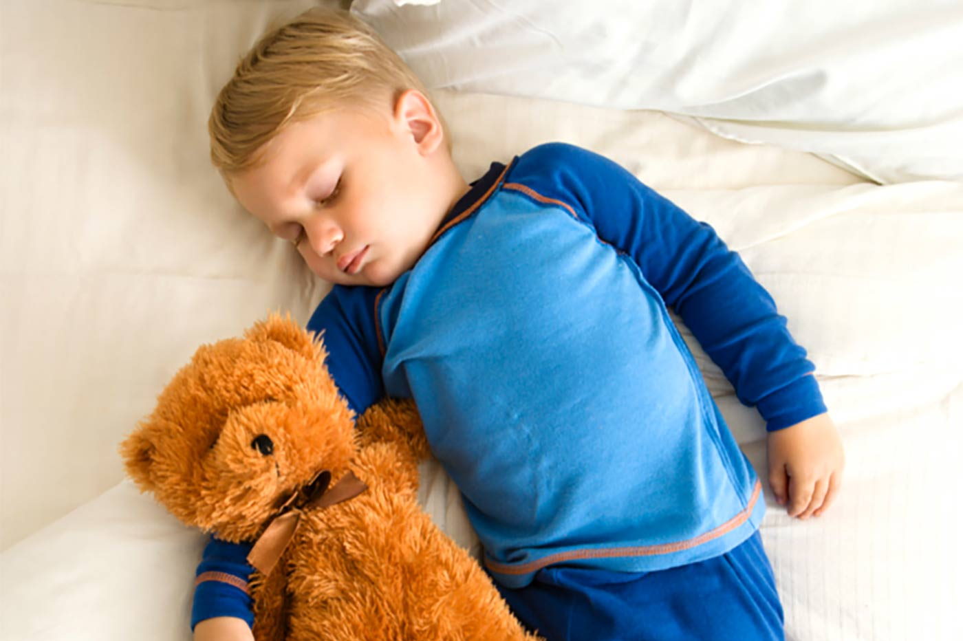 Little boy sleeping with a teddy bear