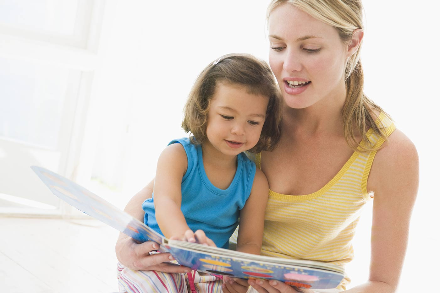 A mom reading with her young daughter children's books about self esteem