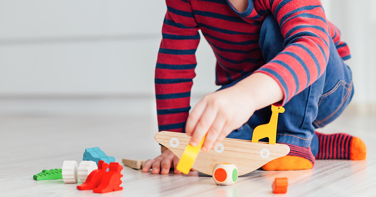 A little boy playing with wooden toys