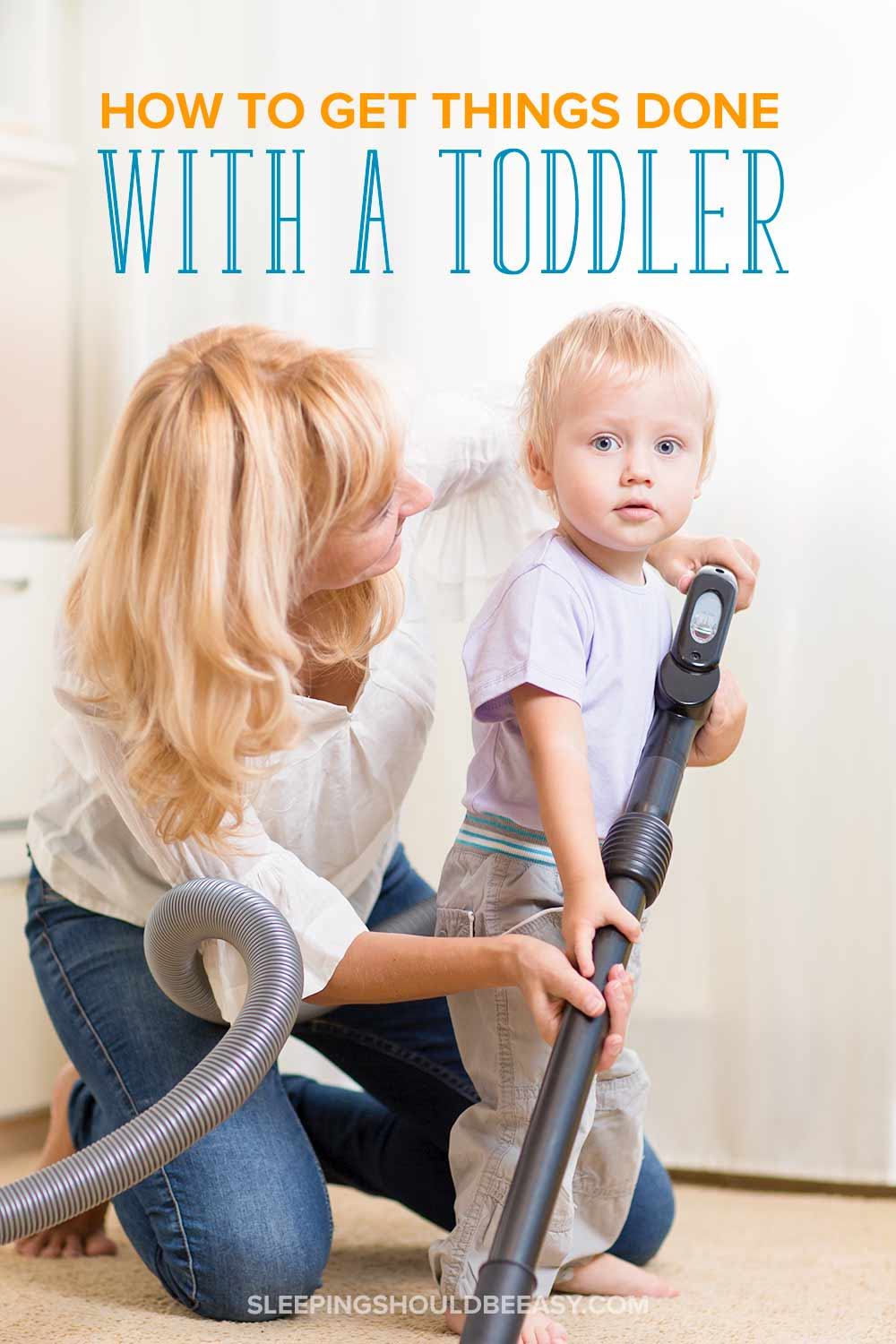 Mom showing her toddler how to hold the vacuum