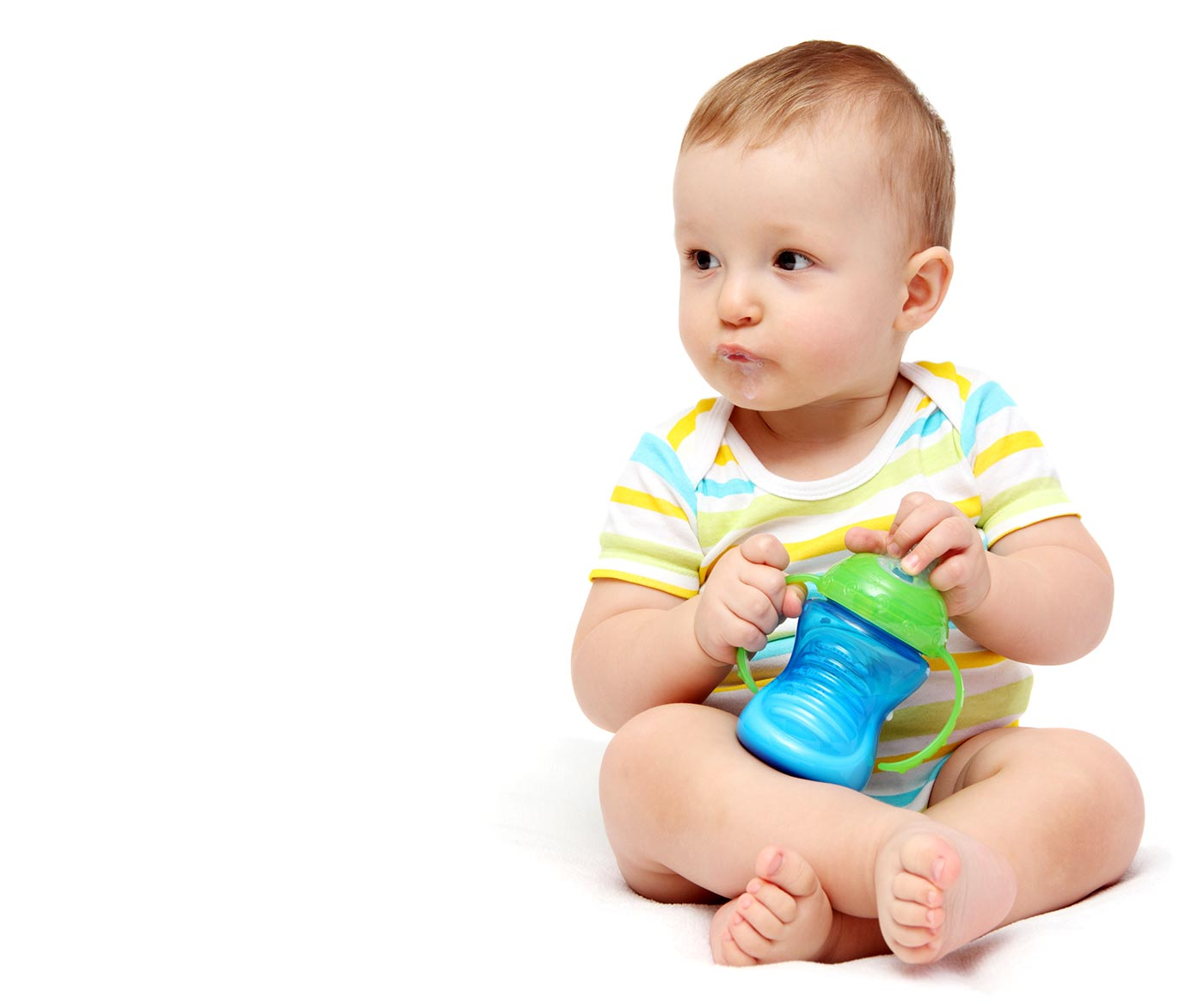Baby holding a sippy cup of milk
