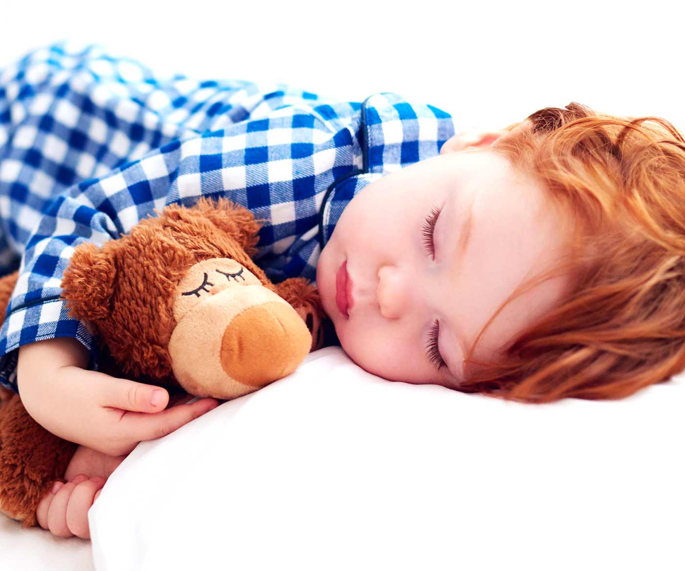 a little boy sleeping with a stuffed animal