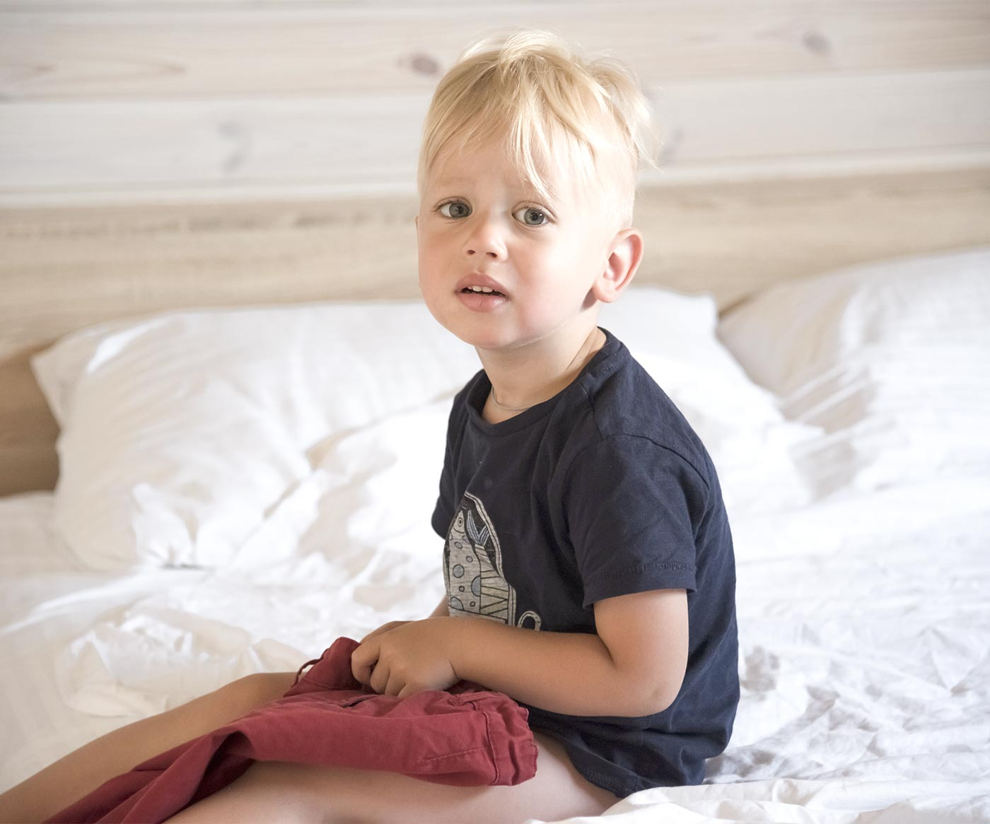 Little boy sitting in bed