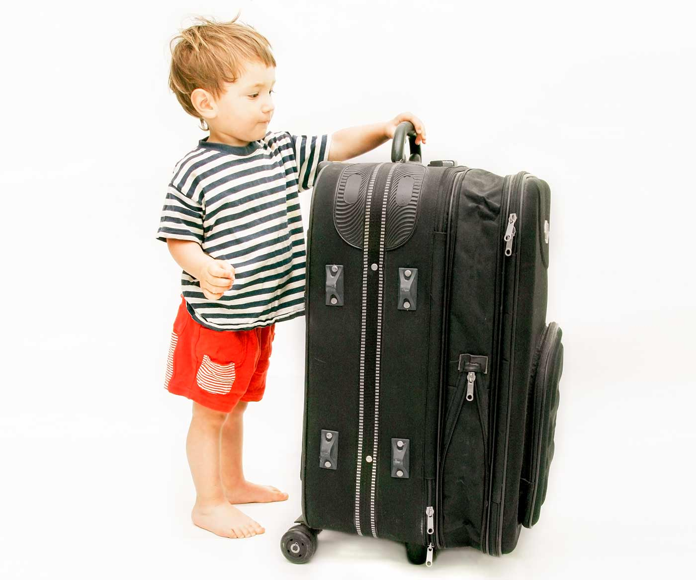 Toddler standing next to a luggage