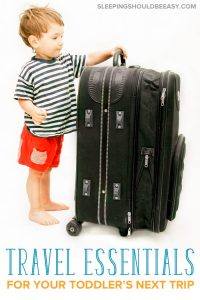 Toddler travel essentials: Toddler standing next to a luggage