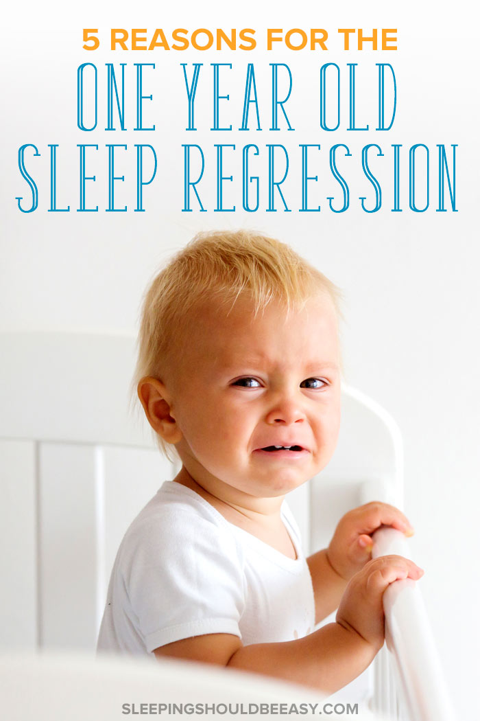 A child standing in his crib, crying because of the 1 year old sleep regression