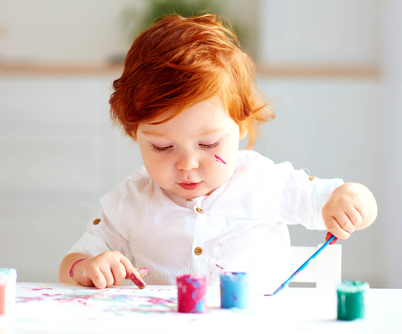 A child painting and doing arts and crafts for 1 year olds