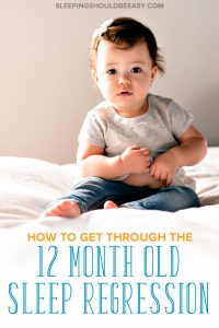 Toddler sitting on a bed going through the 12 month old sleep regression